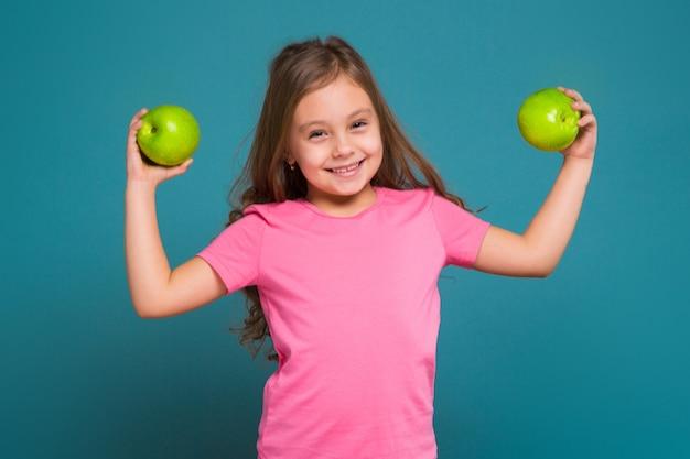 Carina, piccola ragazza in t-shirt con i capelli castani tenere la frutta