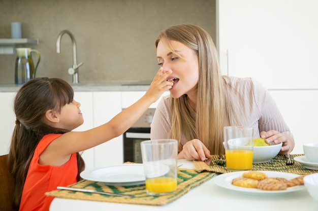 Carina ragazza dai capelli neri che dà il biscotto a sua madre per assaggiare e mordere, facendo colazione con la sua famiglia