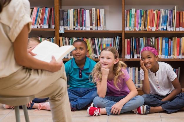 Carino alunni e insegnante avendo classe in biblioteca
