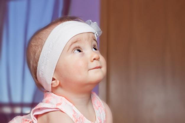 Carino bambino di un anno dall'occhio vigile su qualcosa. in una benda carina.