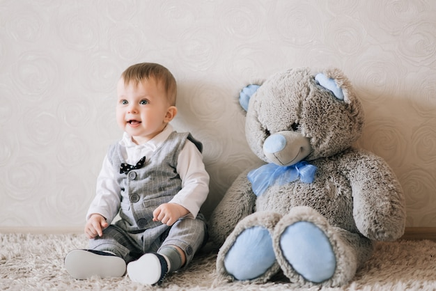 Carino bambino felice in elegante costume da gentiluomo si siede su un tappeto bianco e gioca con il suo orsacchiotto, ridendo del bambino.