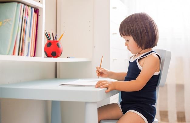 Carino bambino sorridente facendo i compiti, pagine da colorare, scrivere e dipingere