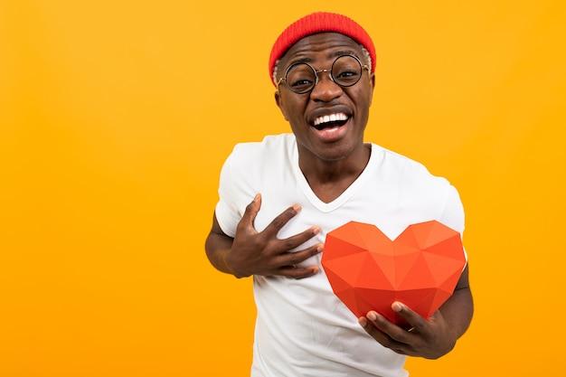 Carino bel americano in una maglietta bianca detiene un cuore rosso 3d fatto di carta per san valentino su uno sfondo giallo