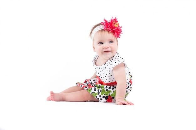 Carino bella bambina in abito a punto con farfalle e involucro rosso