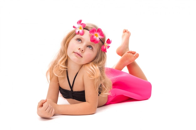 Carino bella bambina in bikini nero, gonna rosa e corona rosa, bugie