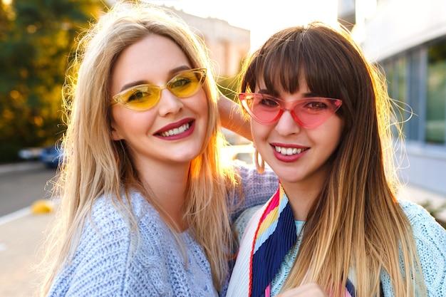 Carino close up soleggiato ritratto di due magnifiche signore piuttosto eleganti sorridenti, con indosso occhiali vintage e maglioni, tempo di primavera autunnale, obiettivi di amicizia.