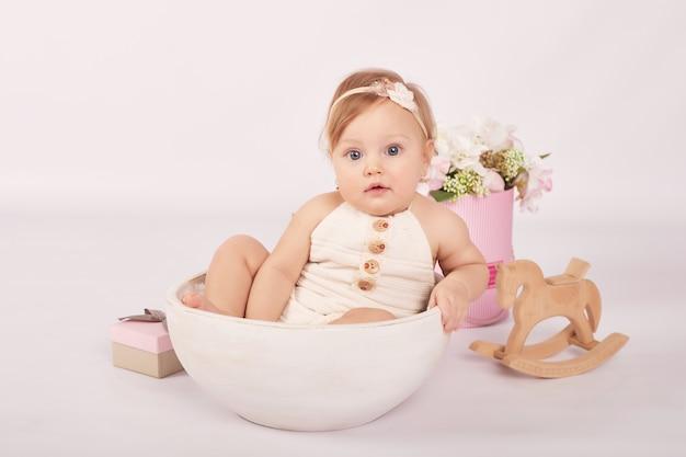 Carino divertente bambino con fiori e giocattoli. bambina carina
