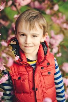 Carino felice ragazzo bambino all'aperto. giorno di primavera. faccia da ragazzino. fiore di primavera rosa sakura. moda per bambini e vestiti alla moda.