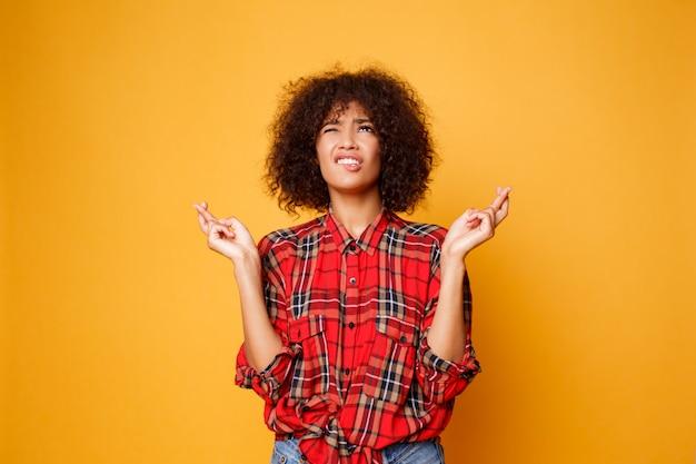 Carino femmina nera emotiva incrocia le dita, spera che tutti i desideri si avverino su sfondo arancione brillante. persone, linguaggio del corpo e felicità.