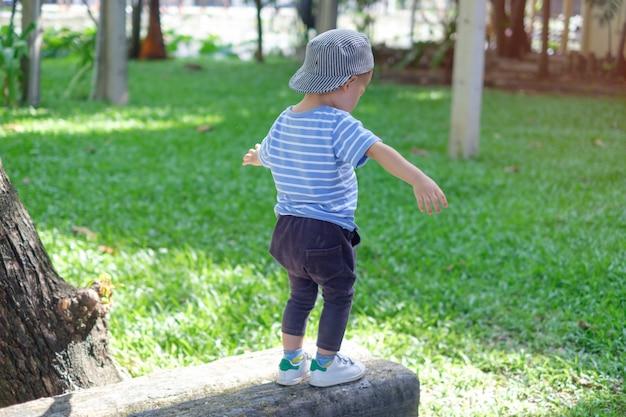Carino piccolo asiatico 18 mesi, 1 anno di età baby boy bambino che cammina sul fascio di equilibrio nel parco sulla natura in estate, fisico, coordinazione mani e occhi, sensoriale, concetto di sviluppo delle abilità motorie