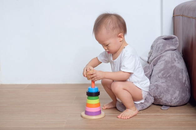Carino piccolo asiatico 18 mesi / 1 anno di età bambino bambino bambino gioca con piramide in legno colorato giocattolo / anello impilabile a
