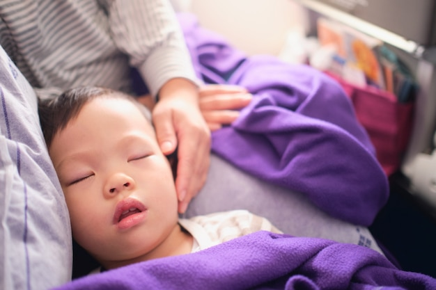 Carino piccolo asiatico 3 anni bambino ragazzo bambino che dorme in aereo, bambino che dorme sui giri della madre durante il volo in aereo, volare con il concetto di bambini