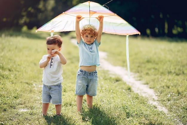 Carino piccolo bambino in un campo estivo con un aquilone