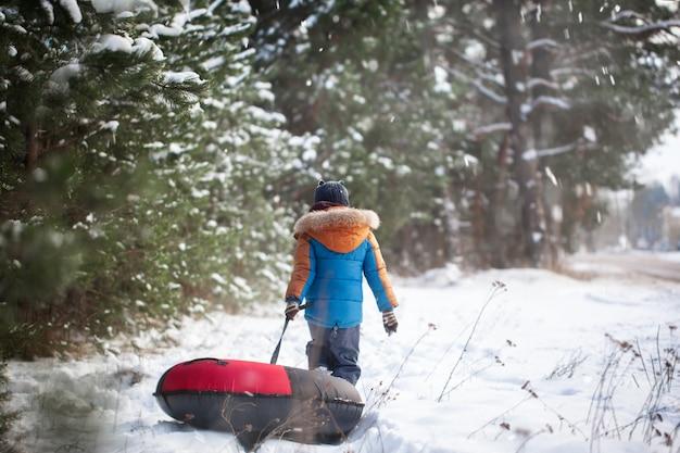 Carino piccolo bambino io. divertendosi sul tubo di neve. il ragazzo sta cavalcando un tubo. vista posteriore