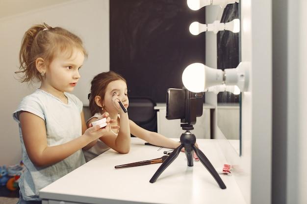 Carino piccolo blogger con cosmetici che registra video a casa