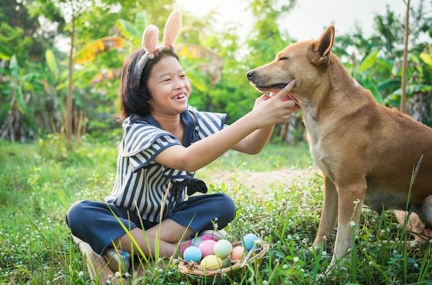 Carino piccolo gril indossando orecchie da coniglio con uova di pasqua e cane.