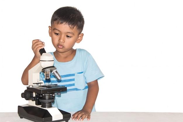 Carino piccolo ragazzo asiatico e microscopio, ragazzino facendo esperimenti scientifici