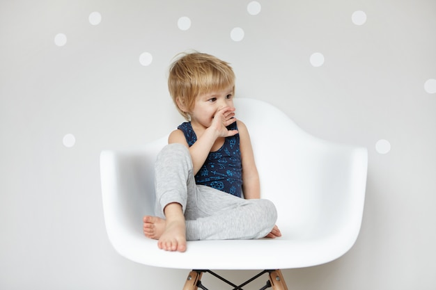 Carino piccolo ragazzo prescolare a piedi nudi biondo in tuta da notte che sembra sorpreso e stupito, coprendosi la bocca, seduto sulla sedia bianca contro il muro con lo spazio della copia per il tuo contenuto