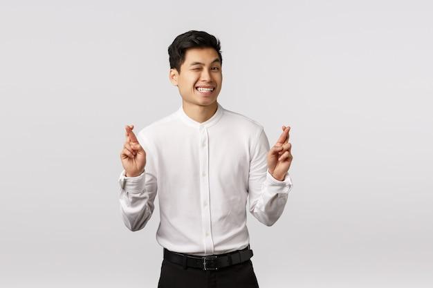Carino promettente ottimista imprenditore maschio asiatico in camicia bianca, pantaloni, occhiolino sfacciato fotocamera, sorridendo assicurato che tutto vada bene, incrocia le dita buona fortuna, anticipa un grosso problema al lavoro firmato