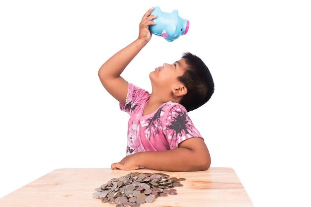 Carino ragazzo asiatico risparmio di denaro nel salvadanaio