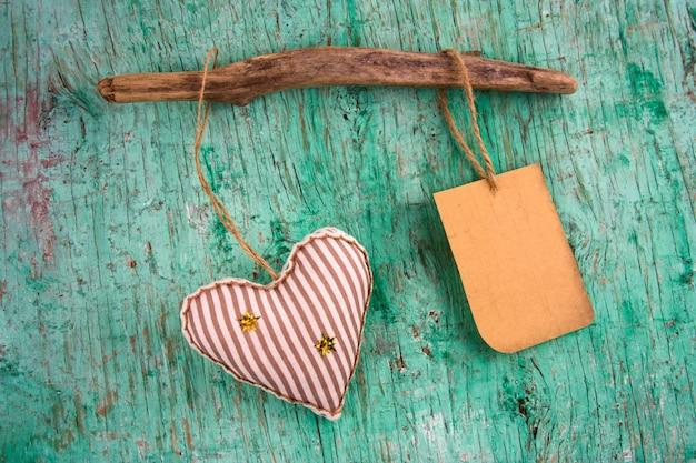 Carino spogliato cuore morbido giocattolo e vecchia etichetta di carta con posto per il testo su un muro d'epoca