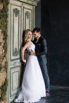 Carino sposi all'interno di uno studio classico decorato. si baciano e si abbracciano.