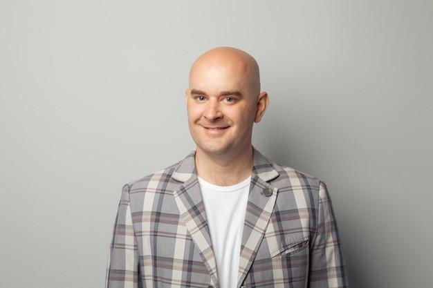 Carino uomo calvo in una giacca e maglietta mostra contro un muro grigio