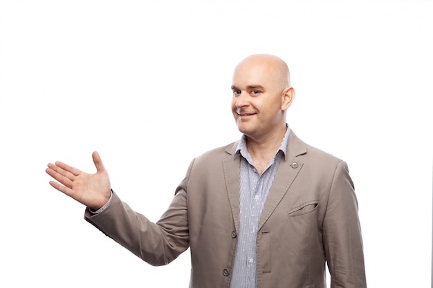 Carino uomo calvo in una giacca mostra contro un muro bianco