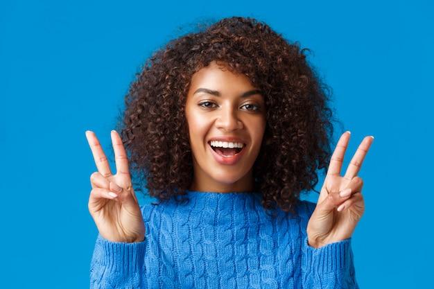 Carismatica eccitata e felice, sorridente allegra donna afro-americana che trasmette vibrazioni positive, mostrando il gesto di pace e sorridendo, godendo le vacanze invernali, festa di capodanno, dire formaggio