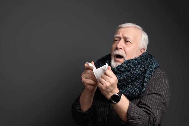 Carismatico uomo di buon cuore avvolto in una sciarpa, con un tovagliolo e uno starnuto, ha preso un raffreddore