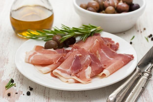 Carne affumicata con olive sul piatto bianco