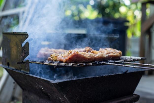 Carne alla bistecca di maiale all'aperto sulla griglia del barbecue, fatta in casa, carne di maiale fatta in casa