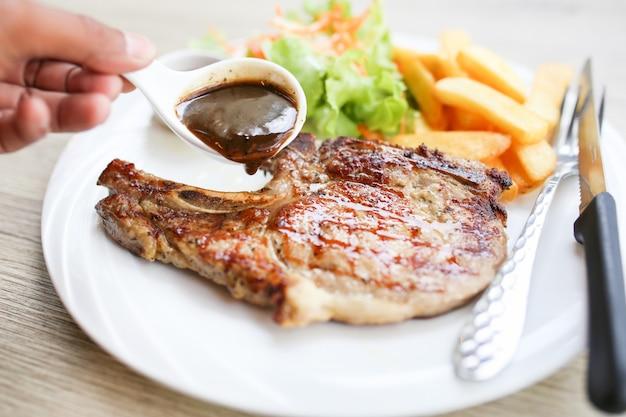 Carne alla griglia, bistecca di maiale con salsa al pepe e insalata.