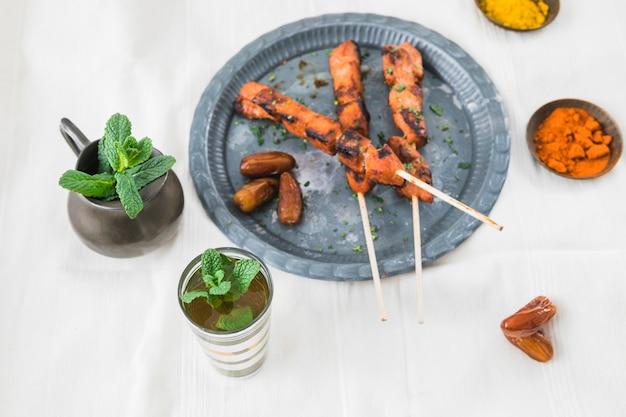 Carne alla griglia con prugne secche vicino a tazza, spezie e brocca