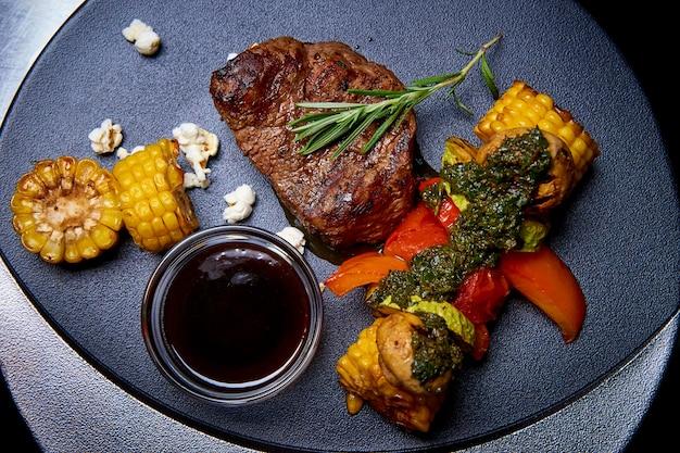 Carne alla griglia con verdure con salsa su un piatto.