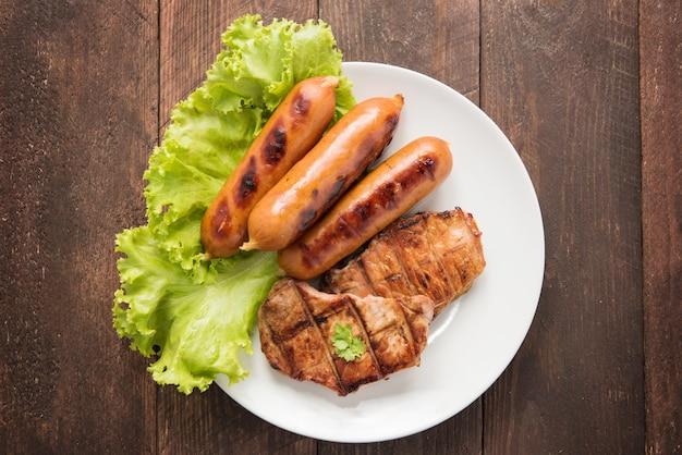 Carne alla griglia, salsicce e verdure sul piatto.