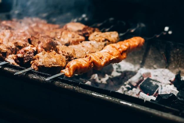 Carne allo spiedo. griglia di maiale. fumare il barbecue in strada. cucinare shashlik di pollo. carboni ardenti.