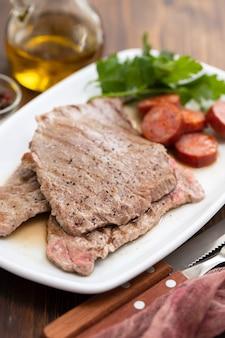 Carne arrostita con la salsiccia affumicata sul piatto bianco