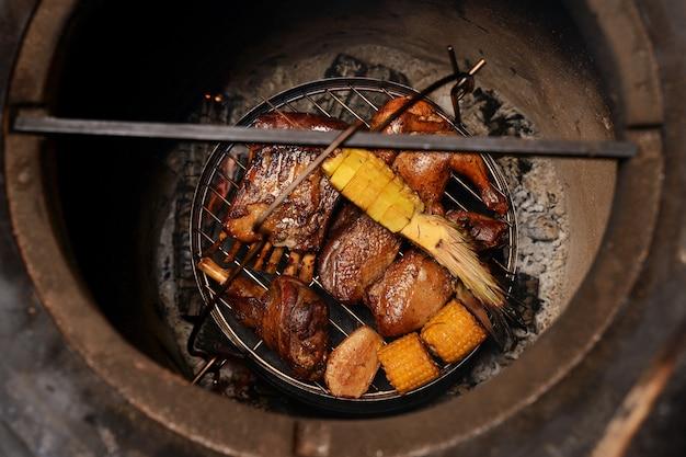 Carne arrostita deliziosa assortita con le verdure sopra i carboni su un barbecue