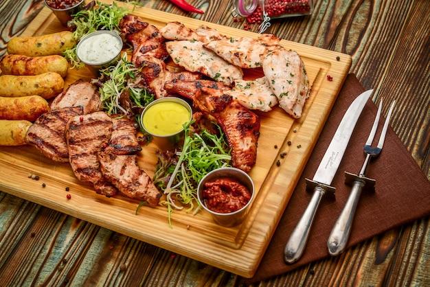 Carne arrostita deliziosa assortita e verdure con insalata fresca e la salsa del bbq sul tagliere su fondo di legno. grande set di piatti caldi di carne
