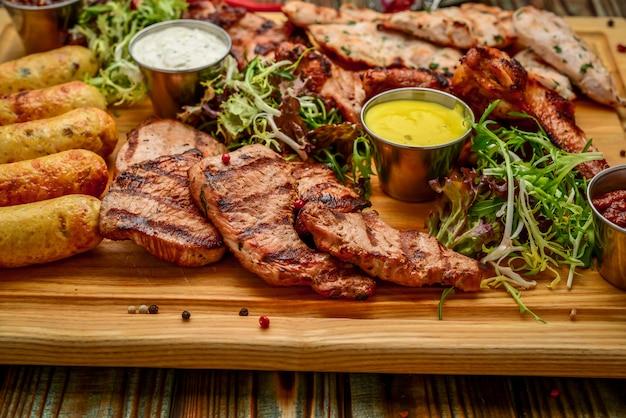 Carne arrostita deliziosa assortita e verdure con insalata fresca e la salsa del bbq sul tagliere su woode