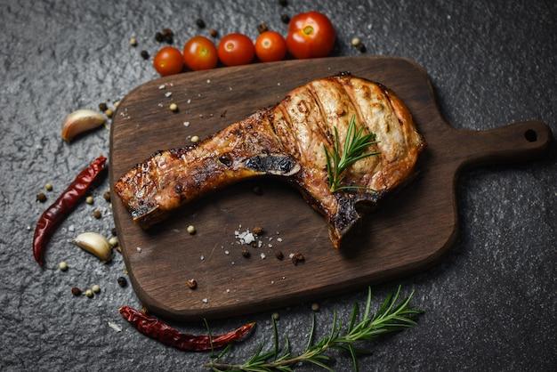Carne arrostita di braciola di maiale su fondo nero - la bistecca di braciole di maiale con l'erba e le spezie serve sul bordo di legno