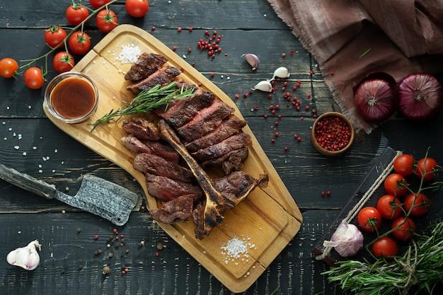 Carne arrosto su un osso e verdure fresche su un tagliere di legno in stile rustico