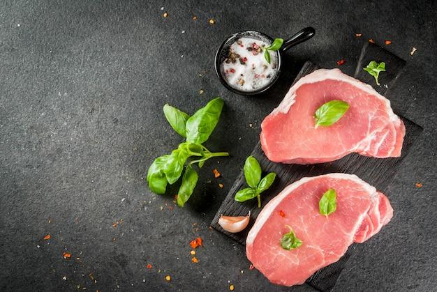 Carne biologica cruda bistecche di maiale, filetti per grigliare, cuocere al forno o friggere. su un tagliere di legno, con sale, pepe, basilico, pomodori, aglio. su un tavolo di pietra grigia. vista dall'alto di copyspace