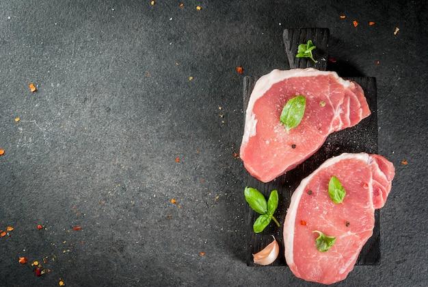 Carne biologica cruda bistecche di maiale, filetti per grigliare, cuocere al forno o friggere. su un tagliere di legno, con sale, pepe, basilico, pomodori, aglio. su un tavolo di pietra grigia. vista dall'alto