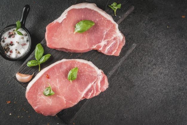 Carne biologica cruda bistecche di maiale, filetti per grigliare, cuocere al forno o friggere. su un tagliere di legno, con sale, pepe, basilico, pomodori, aglio. su un tavolo di pietra grigia.