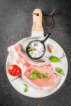 Carne biologica cruda cucina alimentare. maiale con osso. cotoletta per grigliare. con spezie e ingredienti basilico, aglio, sul tavolo nero piatto di marmo bianco tagliere vista dall'alto