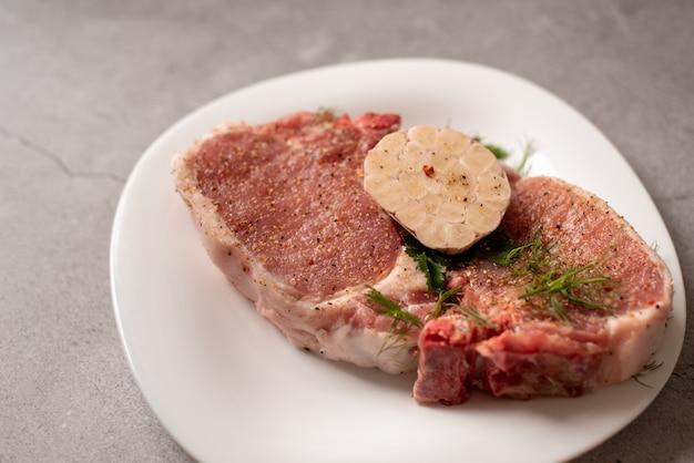 Carne cruda. bistecca di maiale con aneto in un piatto