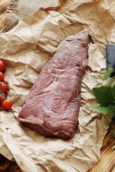 Carne cruda con ingredienti per cucinare il pasto