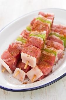 Carne cruda con pepe per la griglia sul piatto bianco sulla tavola di legno